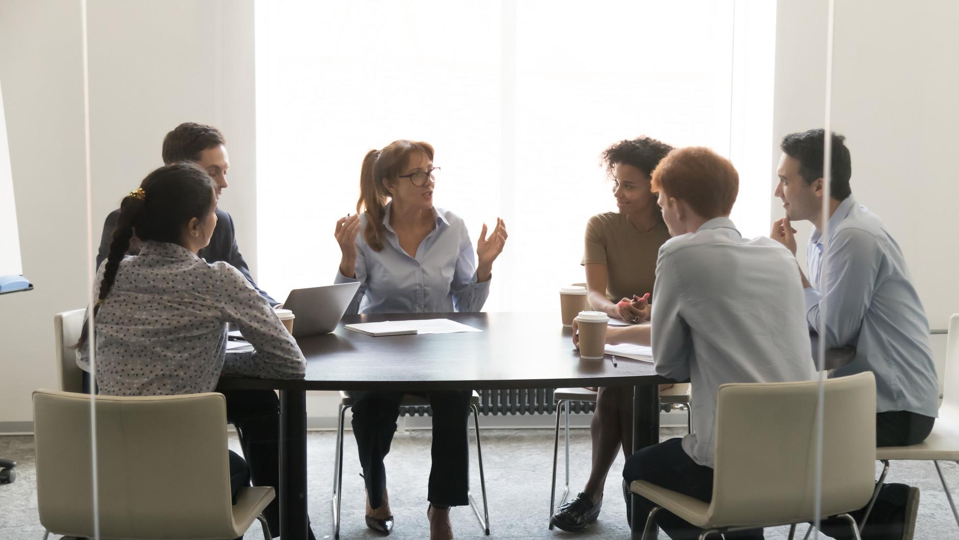 Människor i konferensrum med gestikulerande kvinna i centrum