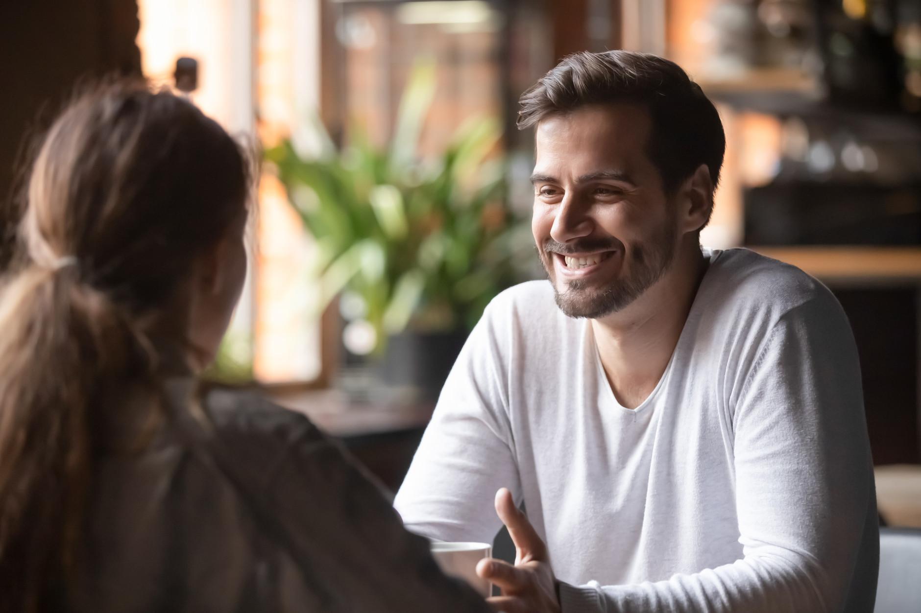 Samtal mellan kvinna och leende man i kafémiljö
