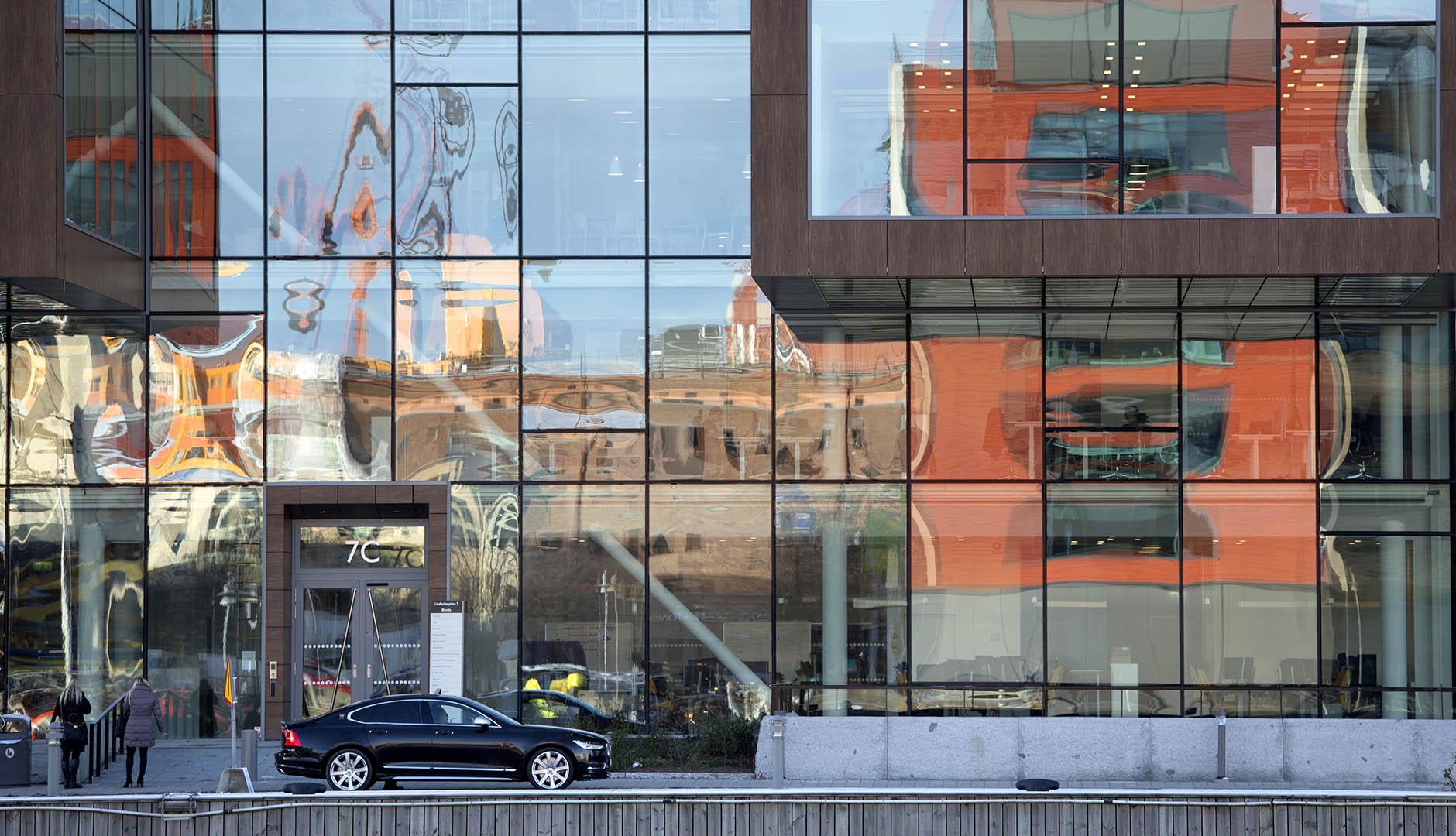 Hus speglar sig i glasfasaden ute på Lindholmen med bil i förgrunden