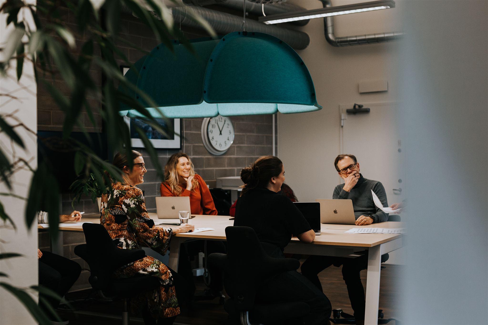 Flera personer som sitter vid ett bord med datorer