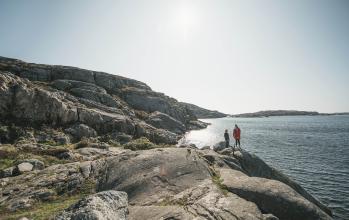 Två person går på klippor vid havet